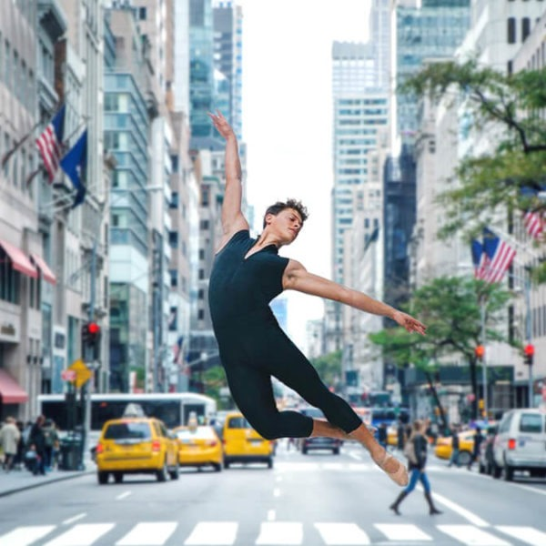 person doing a leap in a busy city intersection